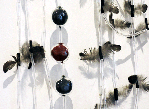 Detail of a necklace made of long, cylindrical glass, feathers, and glass spheres in a row that are filled with dark blue and red material.
